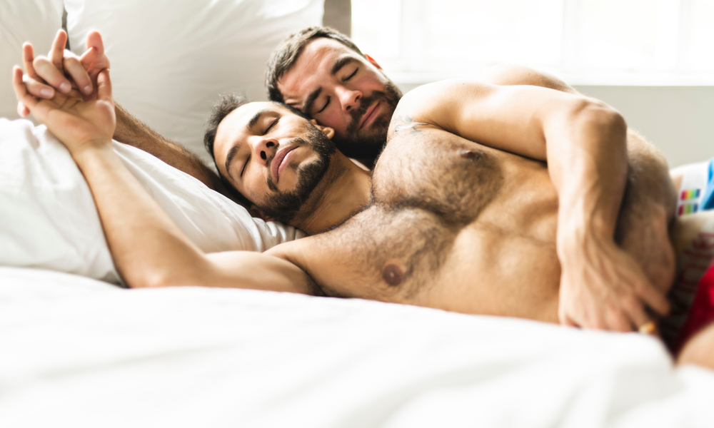 A handsome gay men couple on bed together